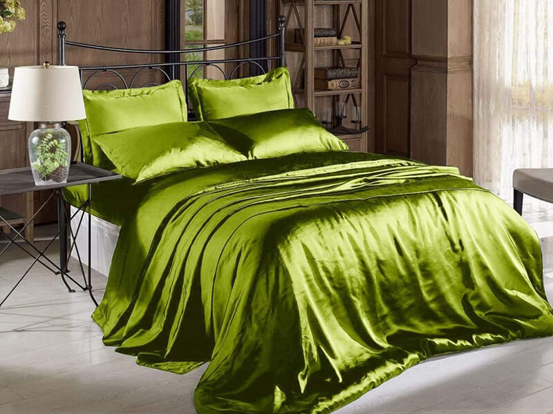 green silky flat sheets set in a room decorated in vintage style