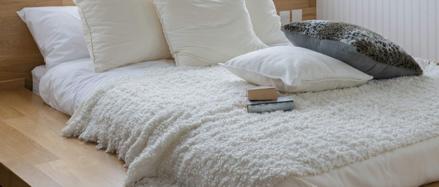 memory foam thin mattress covered with white sheets
