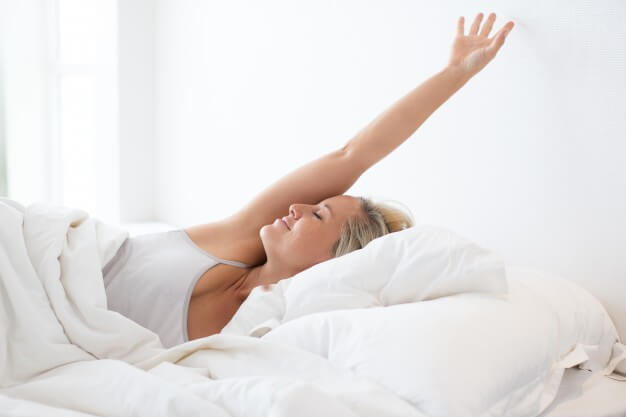 blonde young woman stretching with happy smile in thin mattress after sleep