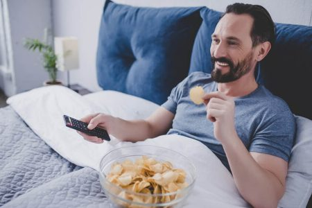 the man with the black beard was lying on the bed with his pillow eating crisps and watching TV